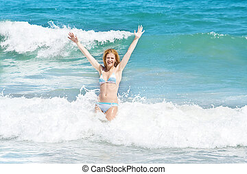 Young woman jumping in the waves on a beautiful tropical beach