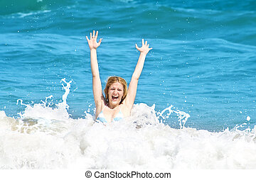 Young woman jumping in the waves on a tropical beach