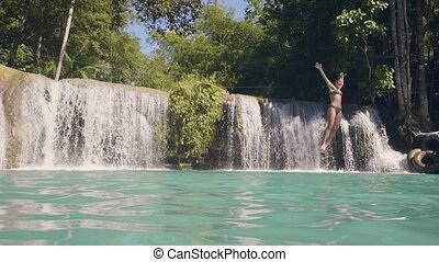 Young woman jumping in waterfall lake from rope and stick...