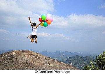 young woman jumping mountain peak