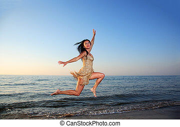 Young woman jumping on a beach