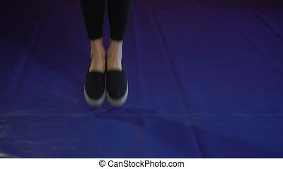 Young woman jumping on a skipping rope in a gym