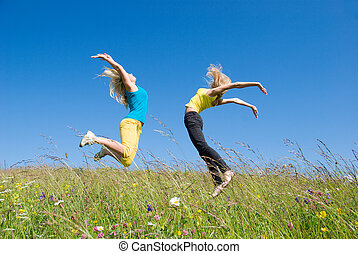 woman jumping on background green meadow