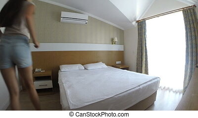 Young woman jumping on bed in hotel room during summer vacation. Slow motion.