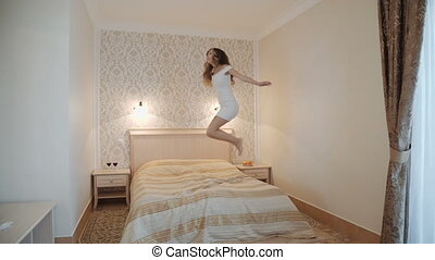 Young woman jumping on bed in luxurious room interior.