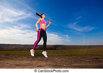 young woman jumping on blue sky background