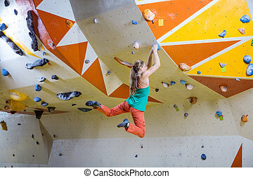 Young woman jumping on handhold in bouldering gym - Young...