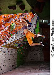 Young woman jumping on handhold while bouldering in climbing...