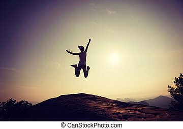 Young woman jumping on rocky mountain peak face the sunrise