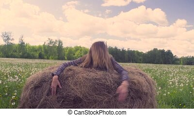 Young woman jumping on the haystack