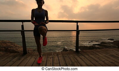 young woman jumping on the sunrise seaside