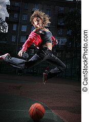 Young woman jumping over basketball ball