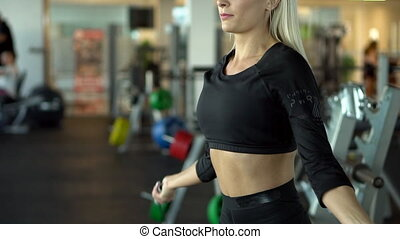 young woman jumping rope in gym, slow motion