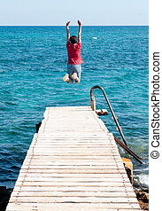Young woman jumping to the sea