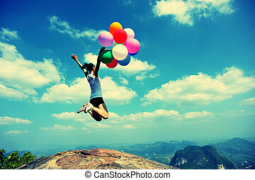 young woman jumping with balloons - young asian woman ...