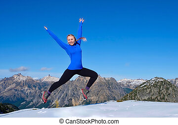 Young woman jumping with joy in mountains.