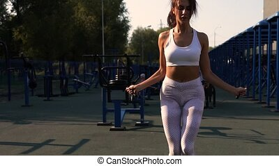 Young Woman Jumping with Rope in Outdoors Gym