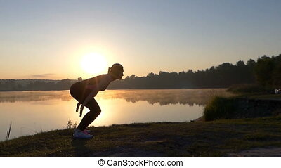 Young woman jumps high on a lake bank at sunset
