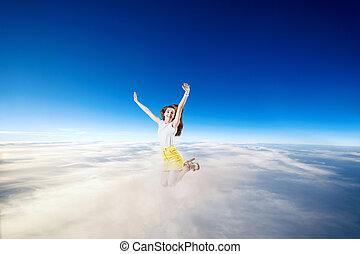 Young woman jumps in the blue cloudy sky.