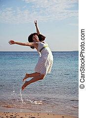 woman jumps  on  sea  beach