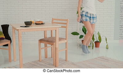 Young woman jumps with joy after hears a good news. Happy girl in pajamas dancing during breakfast. Slow motion.
