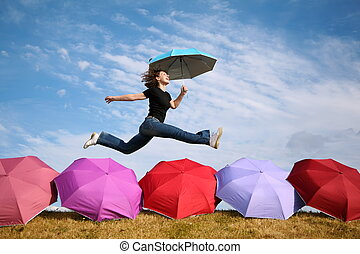 young woman jumps with the umbrella above the umbrellas