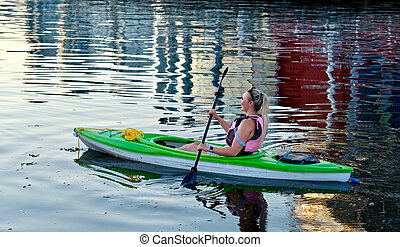 Young woman kayaking paddling  in  the ocean.