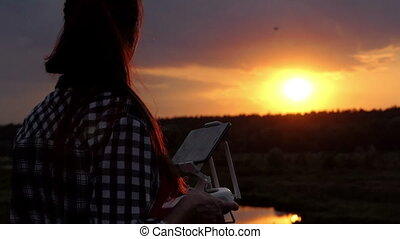 Young woman keeps a panel to control her drone at sunset in slo-mo