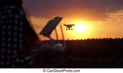 Young woman keeps a panel to manage her drone at sunset in slo-mo