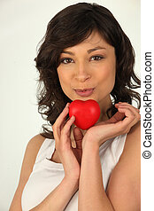Young woman kissing a heart