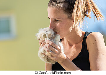 Young woman kissing her pet bunny
