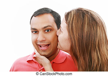 Young woman kissing her surprised boyfriend, isolated on white