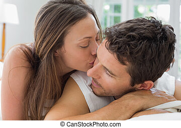 Young woman kissing man in bed - Close-up of a young woman...