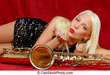 Young woman kissing Saxophone - Pretty young musician sends...