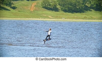 Young woman kitesurfer moving on the river on the kiteboard,...
