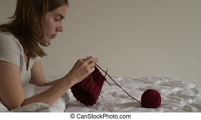 Young woman knitting on a bed
