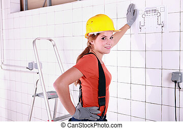 Young woman laborer leaning on a wall