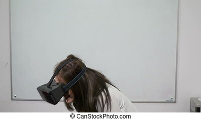 Young woman laughing and having fun in classroom in front of whiteboard while testing virtual reality headset