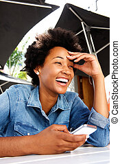Young woman laughing with cell phone outside