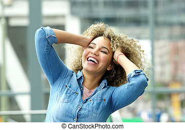 Young woman laughing with hands in hair