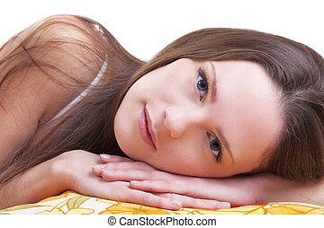 Young woman lay on color pillow and look at you