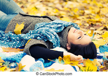 Young woman laying in autumn leaves