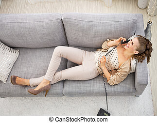 Young woman laying on divan in living room and talking phone