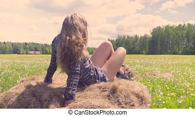 Young woman laying on haystack at summer