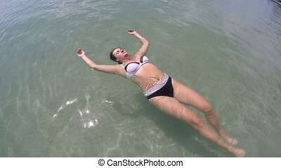Young woman laying relaxing on the waves in beautiful azure...