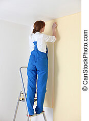 Young woman laying wall paper