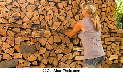 Young woman lays on chopped wood in the woodpile