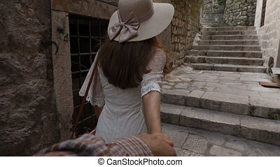 Young Woman Leading a Man to the Adventure in an Old European Town.