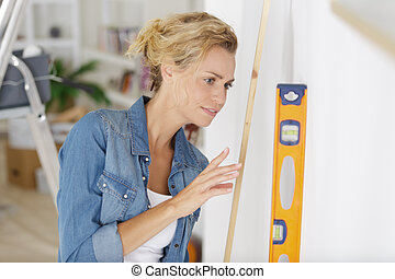 young woman leaning a spirit level on the wall