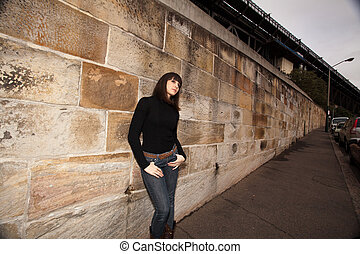 Young woman leaning against a sandstone wall